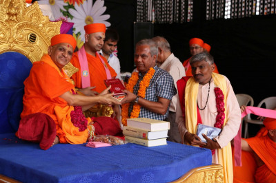 Members of Guljar Chhatra Sahyal Samiti receive scriptures from Acharya Swamishree Maharaj