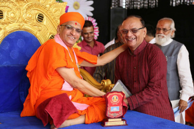 A disciple who attained excellent grades in their education receive a memento from Acharya Swamishree Maharaj