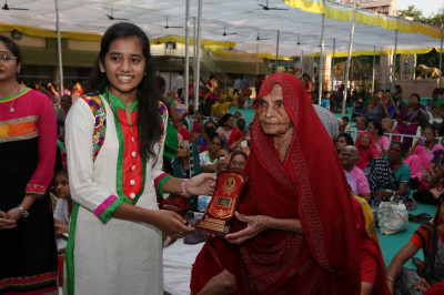 A disciple who attained excellent grades in their education receive a memento from Radha Baa