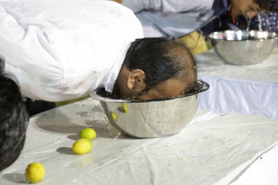Participants attempt to remove limes from a water filled bowl