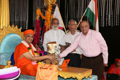 The plaque and mementos are presented to Acharya Swamishree Maharaj