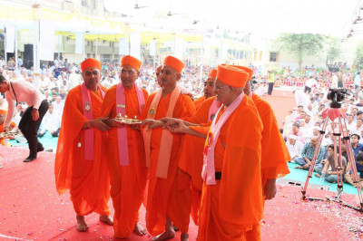 Sants performs aarti to Jeevanpran Swamibapa and Acharya Swamishree Maharaj