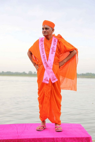 Acharya Swamishree gives darshan on a platform in the river