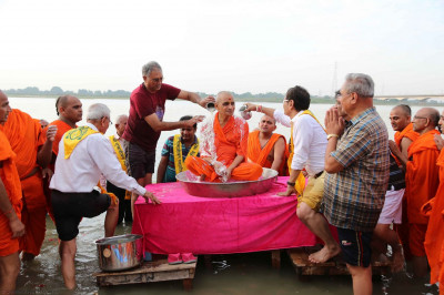 Acharya Swamishree Maharaj being bathed by disciples