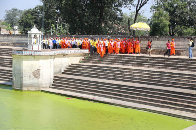 Acharya Swamishree, sants, and disciples walk around the lake
