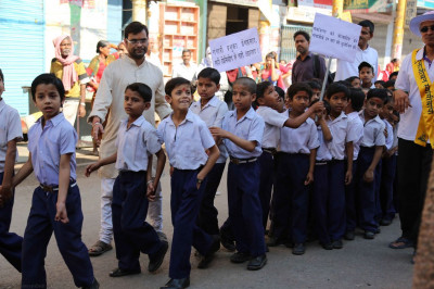 School children march along with the procession