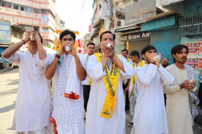 Honourable priests of Kashi blow the auspicious conch shell as at the front of the procession