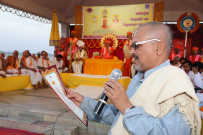 A scholar reads the 'Ved-ratna' which is to be presented to Acharya Swamishree Maharaj