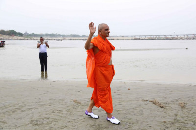 Acharya Swamishree walks along the beach
