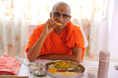 Acharya Swamishree has some prasad