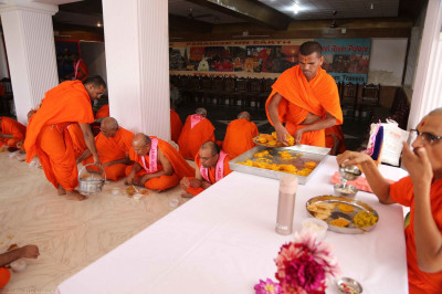 Acharya Swamishree and sants have some prasad
