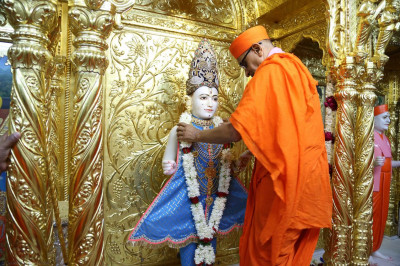Acharya Swamishree puts a garland on Lord Swaminarayan