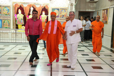 Disciples escort His Divine Holiness Acharya Swamishree through the mandir towards the stage