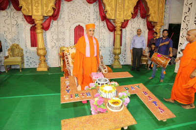 Divine darshan of Acharya Swamishree on stage with the celebratory birthday cakes