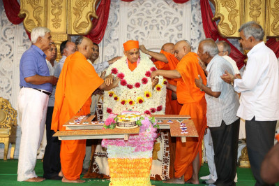 Sants and disciples present His Divine Holiness Acharya Swamishree with a shawl made of fresh fragrant flowers