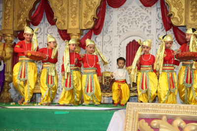 Very young disciples dressed in colourful outfits perform a devotional dance to please the Lord