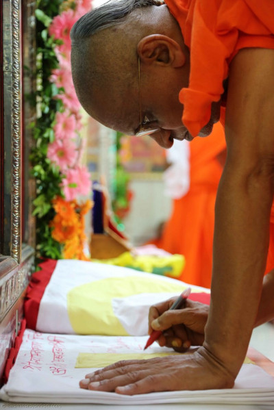 His Divine Holiness Acharya Swamishree inscribes the name of Lord Shree Swaminarayan on the new mandir flags