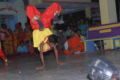 A disciple does an hand stand during the performance