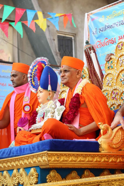 Acharya Swamishree give darshan on a chariot during the procession