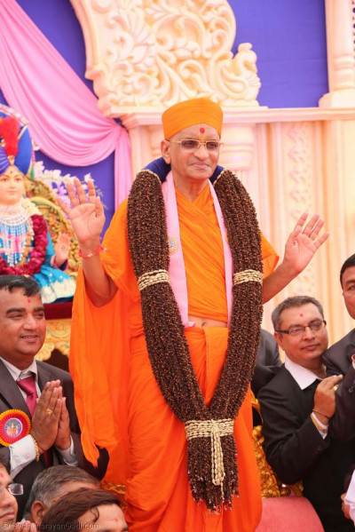 Divine darshan of Acharya Swamishree with a garland made of cloves