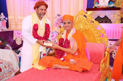 Acharya Swamishree gives prasad to a guest