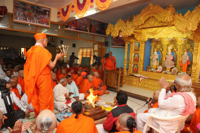 Acharya Swamishree performs aarti during the ceremony