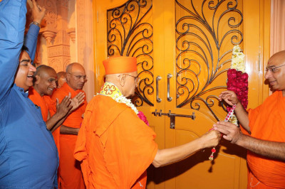 Acharya Swamishree cuts a ribbon to mark the opening of the mandir