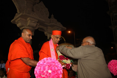A disciple puts a garland on Shree Harikrishna Maharaj