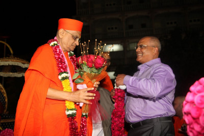 A disciple pust a garland on Acharya Swamishree Maharaj