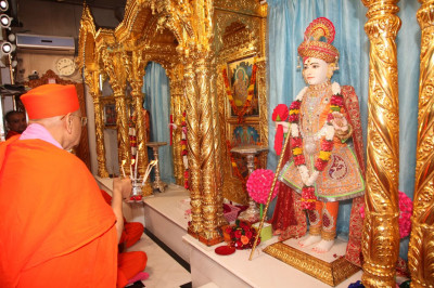 Acharya Swamishree Maharaj performs aarti to Lord Swaminarayan
