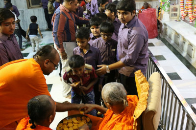 His Divine Holiness Acharya Swamishree presents prasad sweets to all who took part in the evening performances