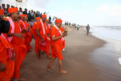 Acharya Swamishree Maharaj walks to the sea with the kalash