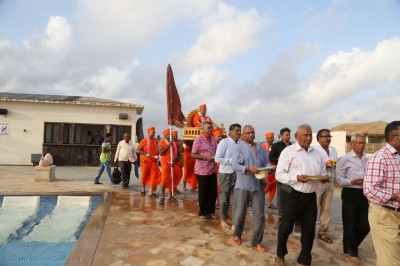 Acharya Swamishree Maharaj is carried on a palanquin to the sabha mandap