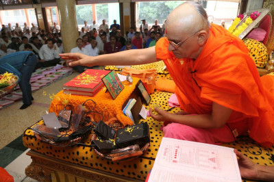 Acharya Swamishree Maharaj concecrates books and devices