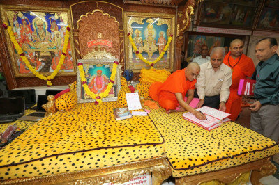 Acharya Swamishree Maharaj conscecrates the mandir accounts books