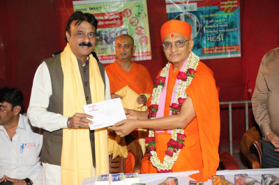 Mayor Gautam Shah receives prasad and memento from Acharya Swamishree Maharaj