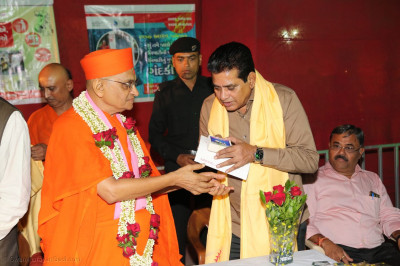 Guests receive prasad from Acharya Swamishree Maharaj