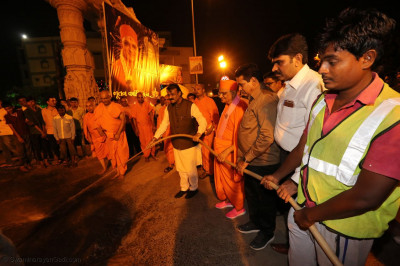 The Mayor and Acharya Swamishree Maharaj uses a water hose to clean the footpath outside the Mandir as part the India's Swachh Bharat Misison