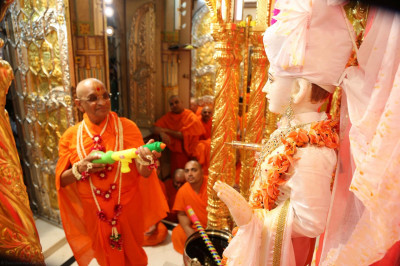 His Divine Holiness Acharya Swamishree sprays colours on Lord Shree Swaminarayan
