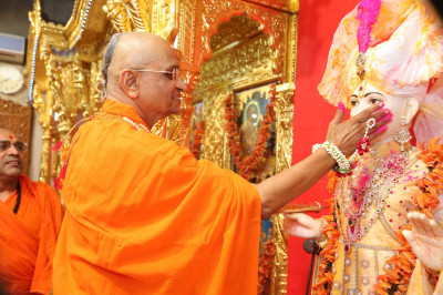 His Divine Holiness Acharya Swamishree lovingly smothers pink coloured powder on the cheeks of Lord Shree Swaminarayan