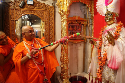 His Divine Holiness Acharya Swamishree sprays colours on Shree Harikrishna Maharaj