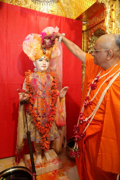 His Divine Holiness Acharya Swamishree pours colours on Lord Shree Swaminarayan
