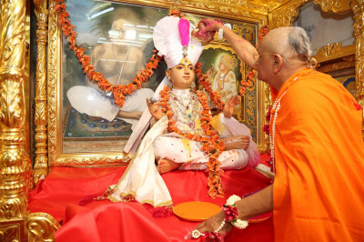 His Divine Holiness Acharya Swamishree pours colours on Shree Sahajanand Swami