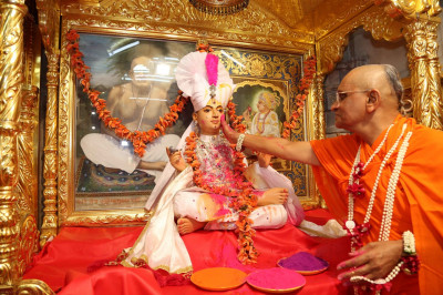 His Divine Holiness Acharya Swamishree sprays colours on Shree Sahajanand Swami