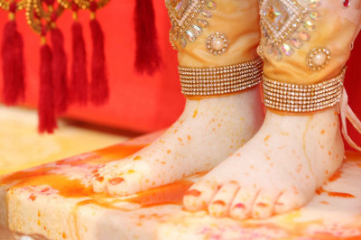 The divine lotus feet of Lord Shree Swaminarayan showered with colour
