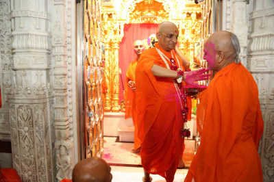 His Divine Holiness Acharya Swamishree somthers all Sants with pink coloured powder