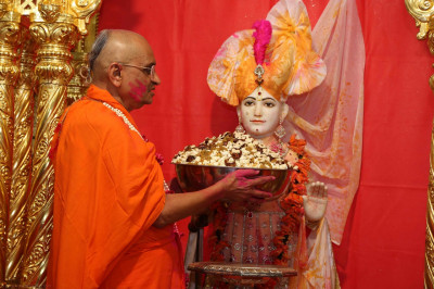 His Divine Holiness Acharya Swamishree feeds popcorn, dried fruit and nuts to Lord Shree Swaminarayan