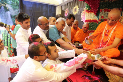 Disciples who have sponsored the celebrations bathe Shree Harikrishna Maharaj with the five nectars