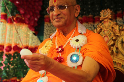 His Divine Holiness Acharya Swamishree holding a loaded water bomb
