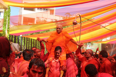 Disciples bathed in colour carry His Divine Holiness Acharya Swamishree
